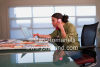 Picture of a woman on the phone and pointing to the screen of her laptop computer. Dark hair pulled back. She is wearing a green blouse.